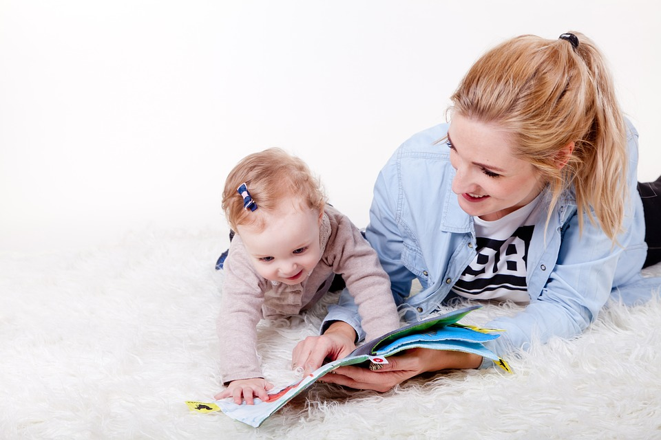 Mom smiling with her baby while looking at a book